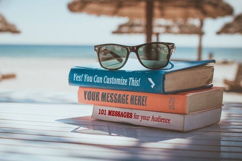 Three books are stacked on a table on the beach in a tropical location. You can customize the book titles using our on-line tools.